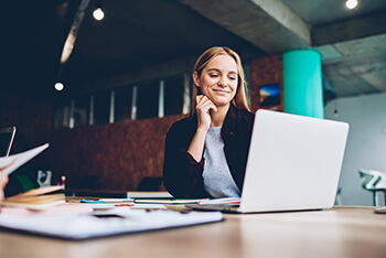 Woman Smiling at Laptop Computer