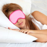 lady laying in bed with eye mask