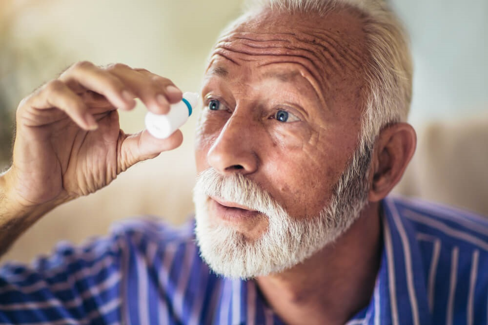Elderly man applying eye drops to manage glaucoma symptoms