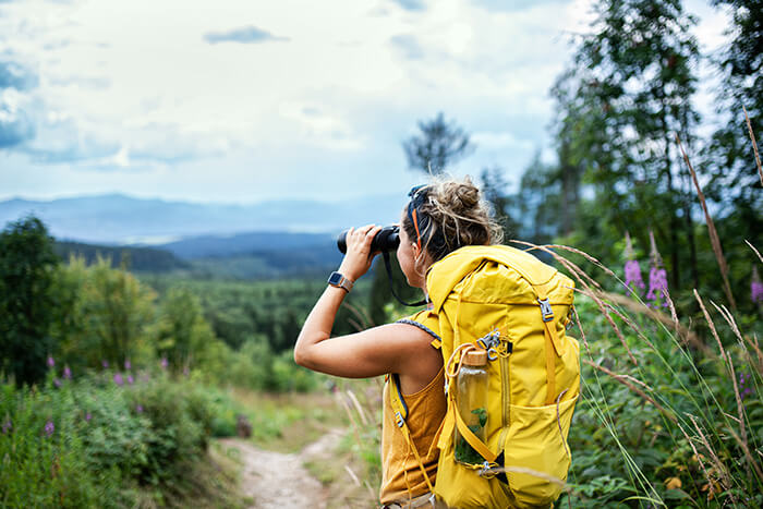 Young woman looking through binoculars while hiking