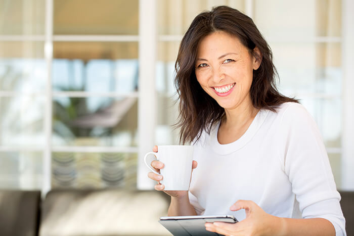 Smiling Middle Aged Woman on her tablet, enjoying some coffee