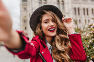 smiling woman wearing red jacket and black hat