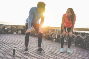 Man and woman break from running and smiling
