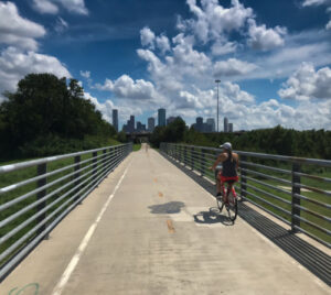 woman riding bike on bridge with city buildings in background