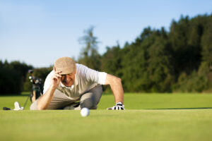 Man looking at golf ball