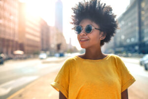 woman in yellow shirt and sunglasses smiling while crossing the street