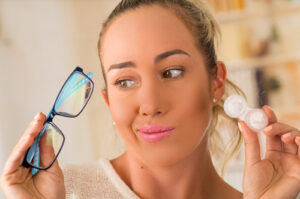 Woman comparing eyeglasses to contact lenses
