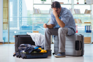 man holding his head while sitting on top of suitcase